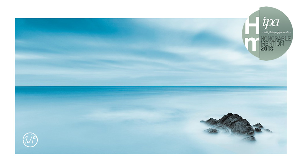 Strong winds stir up the Irish sea to crash upon this lone rock as the clouds rush overhead in this 3 minute long exposure image. by John Dunne.