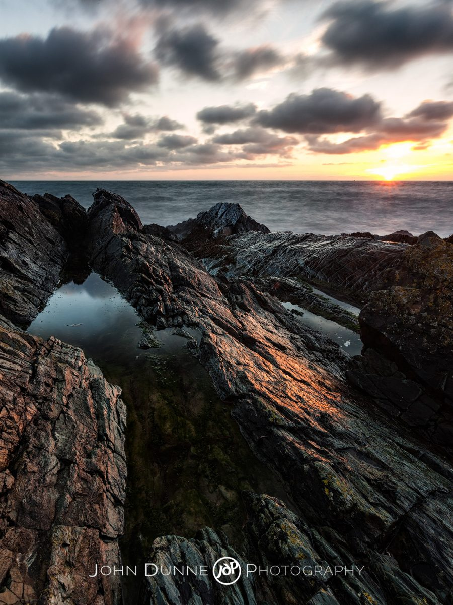The sun is just above the horizon sending soft light upon the rocks of Greystones beach in Co. Wicklow, Ireland by John Dunne.