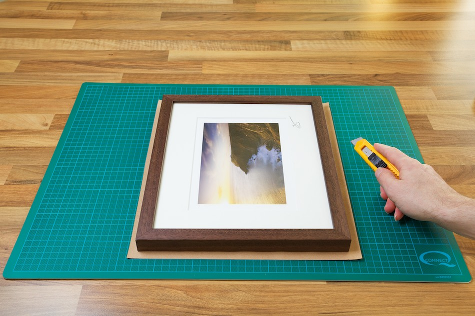 An image showing the Kraft paper being cut to the right size for the frame from John Dunne Photography by John Dunne.