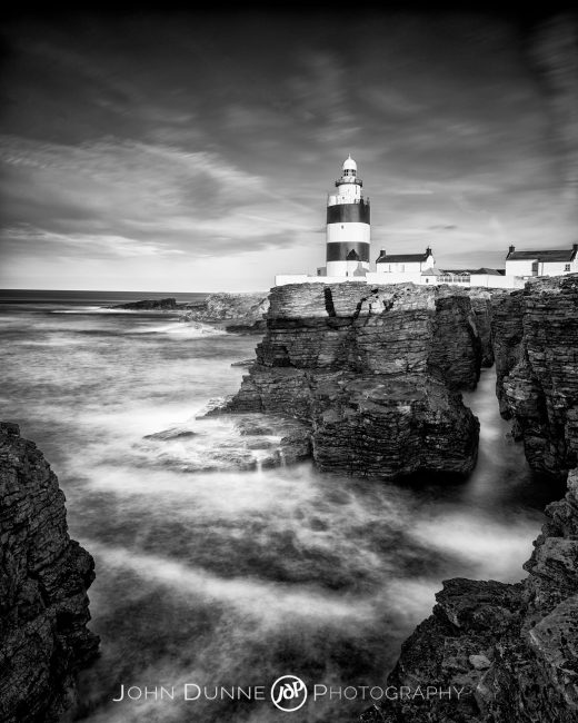 A black and white photograph of Hook Lighthouse in Wexford Ireland, standing firm above turbulent seas.